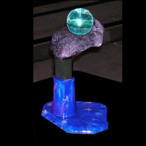 A Pate de Verre hand holding the Earth, set in Wood